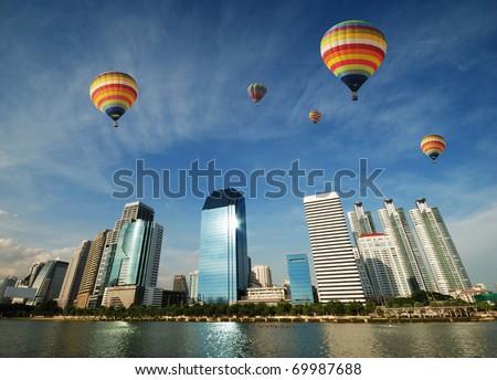 Colorful balloons floating over Bangkok skyscraper