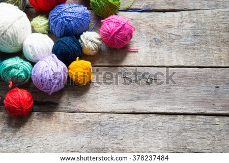 Colorful balls of wool on a wooden background - Shutterstock ID 378237484