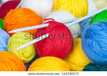 Colorful balls of wool yarn and knitting needles