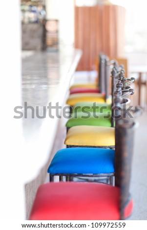 colorful bar stools at an empty bar