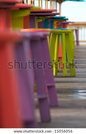 Colorful bar stools in a tropical outdoor bar and restaurant with a selective, shallow focus