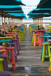 Colorful bar tables, stools and umbrellas at a beach-side bar and restaurant