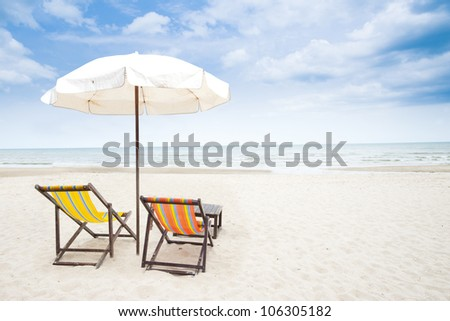 Colorful beach chairs on the white sand beach with cloudy blue sky - stock photo