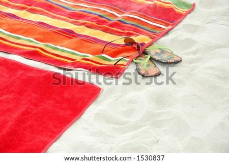 Colorful beach towels on sandy beach