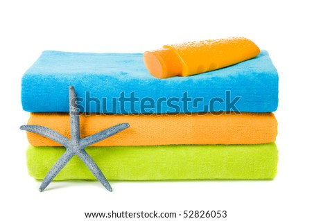 Colorful beach towels with suntan lotion and starfish on white background