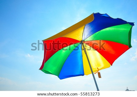 colorful beach umbrella against the sun light - stock photo