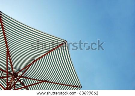 Colorful beach umbrella against the sun light