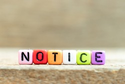 Colorful bead with black letter in word notice on wood background