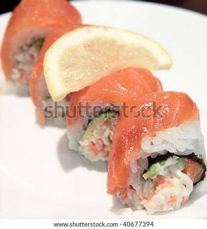 Colorful beautifully arranged sushi roll on a plate with a slice of lemon