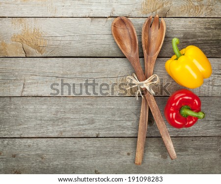 Colorful bell peppers and kitchen utensils over wooden table background with copy space