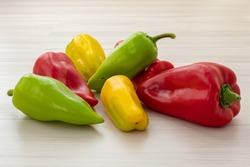 Colorful bell peppers (Capsicum annuum) vegetables. Yellow green red paprika on light wooden background. Bio food for preparing healthy nourishment. Fresh organic products in bright different colors.