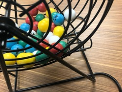 Colorful bingo balls in the selection cage sitting on a wooden desk. The number B11 is showing.