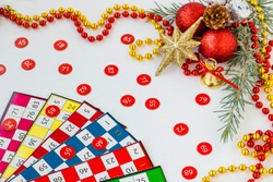 Colorful bingo game cards and numbers on white background with christmas ornaments