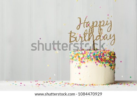 Colorful birthday cake with golden happy birthday banner and falling sprinkles