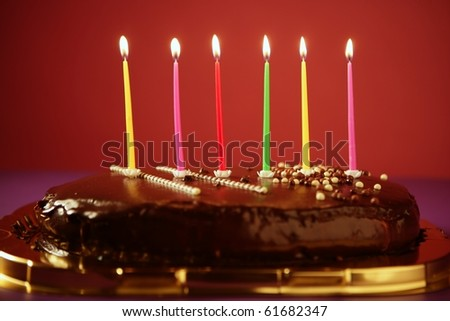 Colorful birthday light candles in a chocolate cake red background