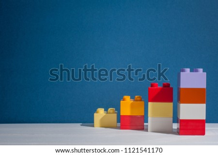 Colorful block toys forming stairs shape over blue background.Symbolic of work hard to success or step to success. #1121541170