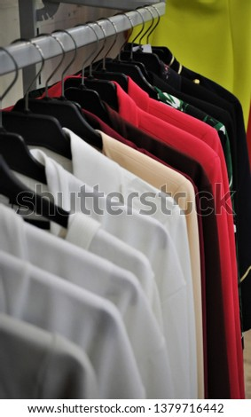Colorful blouses and jackets on rock with hangers.