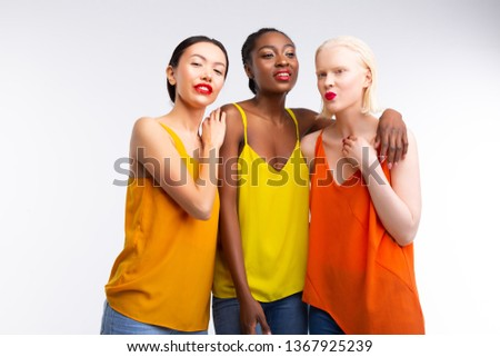 Colorful blouses. Appealing good-looking women with different skin wearing jeans and colorful blouses