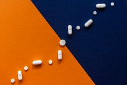 Colorful blue orange background with white pills in form graph. Medical concept of a health, pharmacy and healthcare