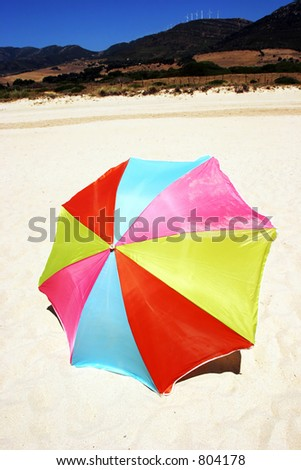 Colorful, blue, red, yellow and pink round umbrella or parasol on white, deserted, sandy beach with sunny blue sky.