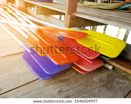 Colorful boat paddles on wood background #1046004997