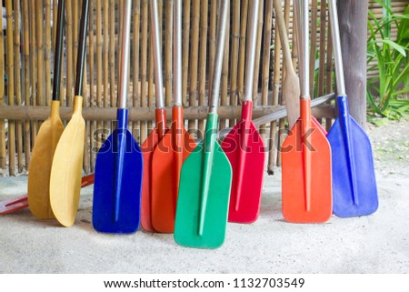 Colorful boat paddles place at bamboo wood wall for tourist #1132703549