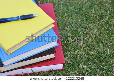 colorful books and pen on grass at a campus