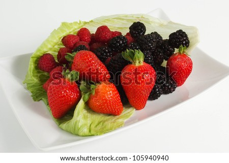 Colorful border frame made of sweet forest berries with blossom isolated on a white background Forest Fruit, strawberries, blueberries, raspberries