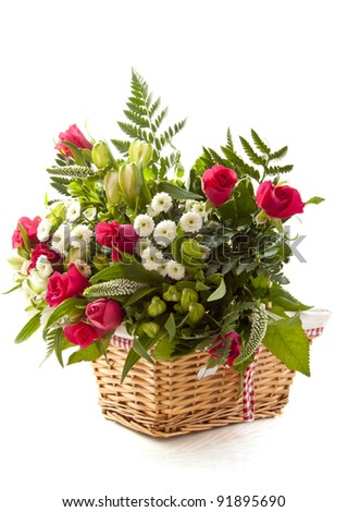 Colorful bouquet in wooden basket over white