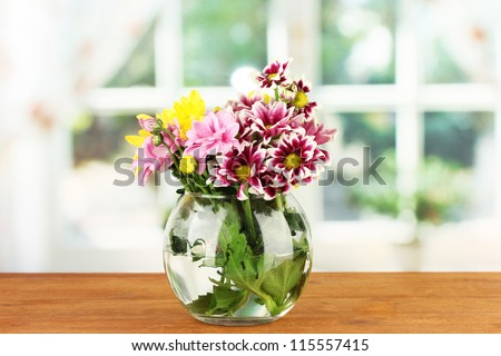 colorful bouquet of chrysanthemums in a glass vase on wooden table close-up - stock photo