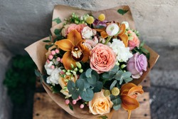 Colorful  bouquet of different fresh flowers against brick wall. Bunch of orchids, roses, freesia and eucalyptus leaves. Rustic flower background. Top view