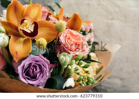 Colorful  bouquet of different fresh flowers. Bunch of orchids, roses, freesia and eucalyptus leaves. Rustic flower background. Close up #623779310