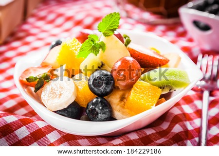 Colorful bowl of tropical fruit salad with blueberries, kiwifruit, orange, apple, banana, grapes and orange for a healthy summer picnic