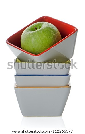 Colorful bowls stacked one above the other with green apple on white background.