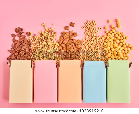Colorful boxes of cornflakes or cereal of different types on pink background, top view #1033915210