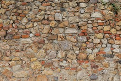 Colorful brick wall with structure of white, grey and brown stones, uneven and empty facade as a background with space for text