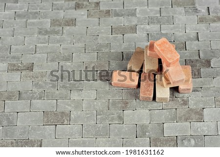 Colorful bricks on a pile. Brick texture close up. The blocks are stacked on brick paving. Copy space and free space near the brick.