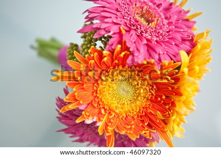 Colorful bridesmaid's bouquet with pink, yellow, and orange flowers.