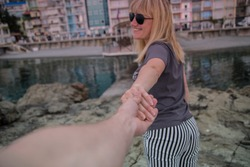 colorful, bright hotels stand on the shores of the blue, clear sea. The girl with blond hair laughs and pulls the guy's hand
