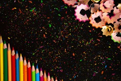 colorful bright pencils and pencil trimmings on a black background