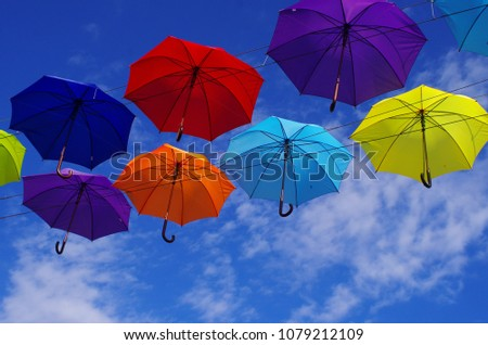 colorful bright umbrellas  street decoration against a blue sky with clouds #1079212109