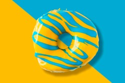 Colorful bright yellow and blue glazed  appetizing doughnut on split color background. Top view of yummy looking donut.