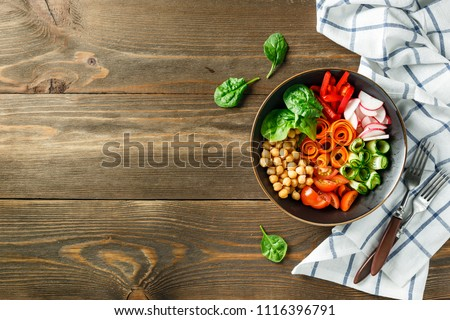 Colorful Buddha Bowl with chickpeas, carrots, tomatoes, cucumbers, radish and peppers on a wooden table. Vegetarian salad. Top view. Space for text.