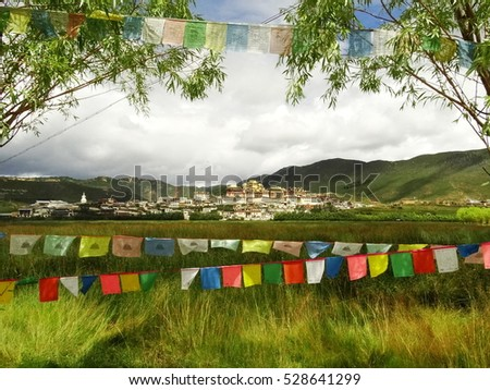 Colorful Buddhist Prayer flags across the lake near Songzanln Monastery in Shangri-La, Yunnan, China, near Tibet  (Tibetan Buddhism, Vajrayana) situated above the lake and among the green mountains. #528641299