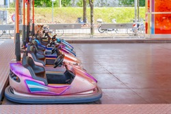 Colorful bumper cars for children in line.