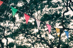 Colorful bunting and round bulb lighting decoration in evening outdoor summer festival with leaves tree background in city park. Summer holiday festival and celebration party concept