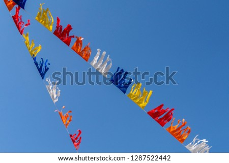 colorful bunting flags against a blue saturated sky #1287522442