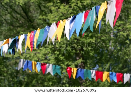 colorful bunting flags against green forest - stock photo