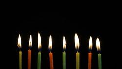 colorful burning candles set on black background.