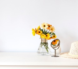 Colorful calendula flowers in a vase on the white table composition. Copy space